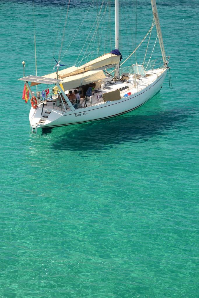 Visto desde lo alto, el Tam-Tam parece volar sobre un agua de cristal, proyectando su sombra sobre el fondo de esta cala en Ibiza.