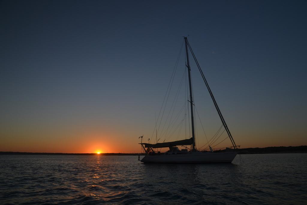 Cae la noche en una tranquila bahia del sur de Formentera. Mientras se prepara la cena, los participantes en el crucero se reunen y charlan en cubierta, bajo las estrellas.