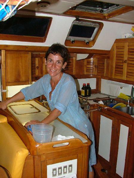 Ana en el interior de nuestro velero, preparando las cosas para la cena durante uno de los charter en Baleares.