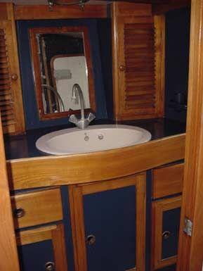 Vista parcial del baño de proa, acabado en madera maciza de cerezo.