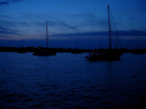 Cae la noche en una tranquila bahia del sur de Menorca. Mientras se prepara la cena, los participantes en el crucero se reunen y charlan en cubierta, bajo las estrellas.