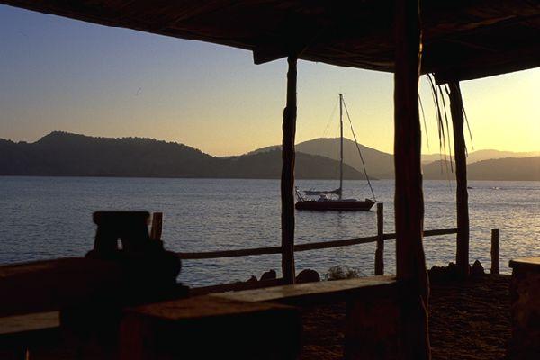 Sentados en torno a unas cervezas, en un chiringuito de la playa, contemplamos el Tam-Tam fondeado en la bahia frente a nosotros. Estamos en el sur de Ibiza.