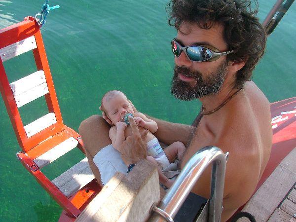 Antonio con su niña, la pequeña Tula, a la que muestra las transparentes aguas de una cala en Baleares. Algun dia sera una gran marinera.